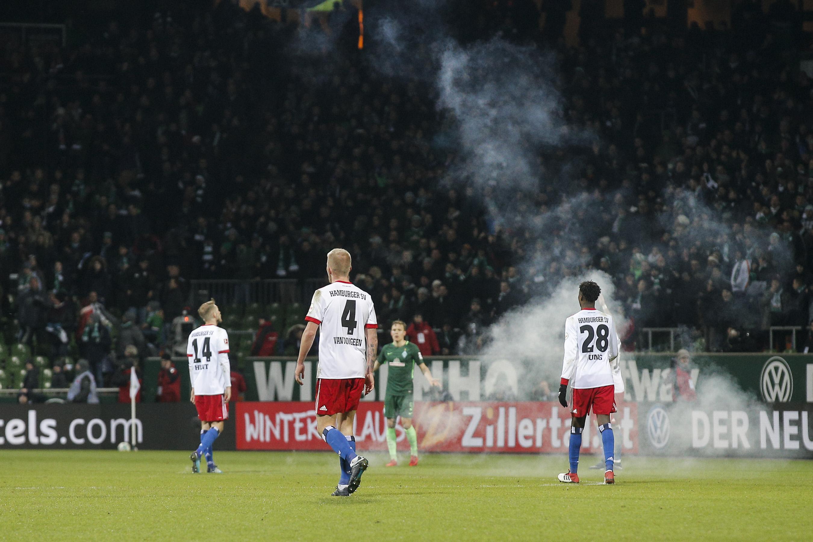 Die Hamburger Fans werfen Brandsätze auf das Feld.